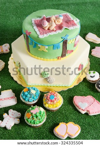 a baptism cake with others colorful candies in the grass - stock photo