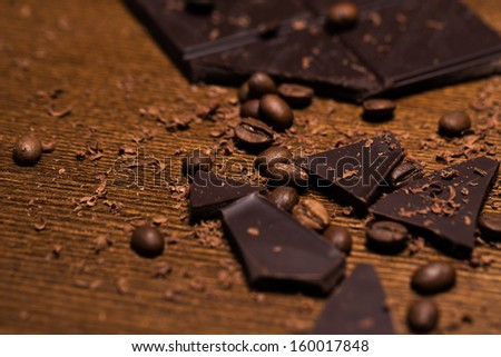 A bar of dark chocolate and some coffee beans on a wooden surface - stock photo