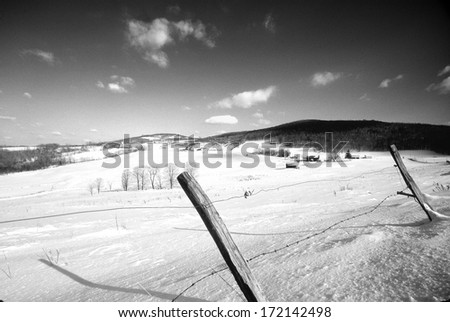 A barbed wire fence in winter against a snow covered landscape makes a striking composition. - stock photo