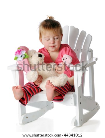 A barefoot baby sleeping as she rocks her mama and baby Teddy bear.  Isolated on white. - stock photo