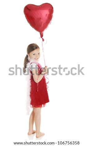 A barefoot elementary girl smiling back over her shoulder while holding a heart-shaped balloon.  She's dressed in red with a fluffy white boa and strands of hearts.  On a white background. - stock photo