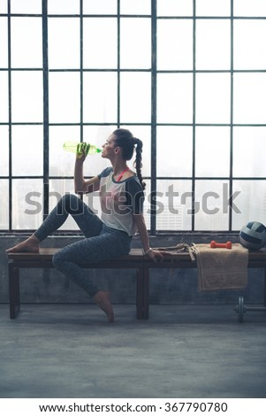 A barefoot, fit woman in workout gear is sitting on a bench by the window in a loft gym, drinking refreshing water after a good workout. - stock photo