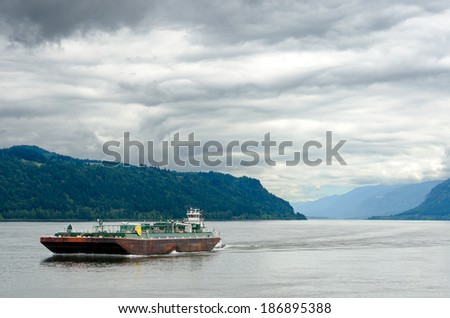 A barge passing through the Columbia River Gorge between Oregon and Washington - stock photo