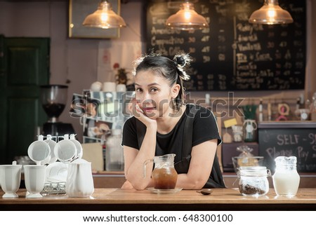 A barista girl is cooking a cup of ice Americano coffee.