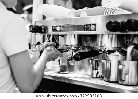 A barista prepares a hot shot of espresso, the coffee dripping down from a nice espresso machine in a coffee shop. Horizontal image.