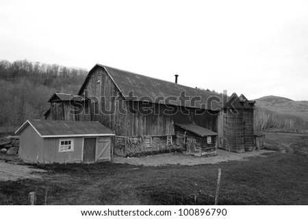 A barn on a field next to the woods - stock photo