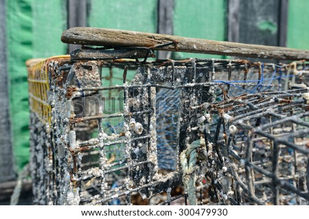 A barnacle encrusted lobster trap awaits maintenance on a working dock - stock photo