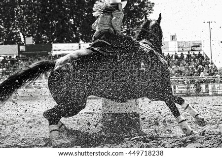 A barrel racer at a rodeo makes an explosive turn around one of the barrels, sending arena sand flying in all directions, as the athletic horse and rider try to win the rodeo (black and white image). - stock photo