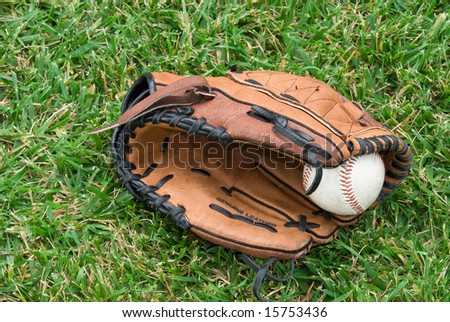 A baseball glove and ball lie in the grass before a game.