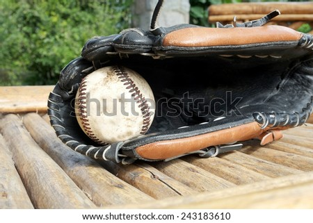 A baseball glove with a dirty old ball inside - stock photo