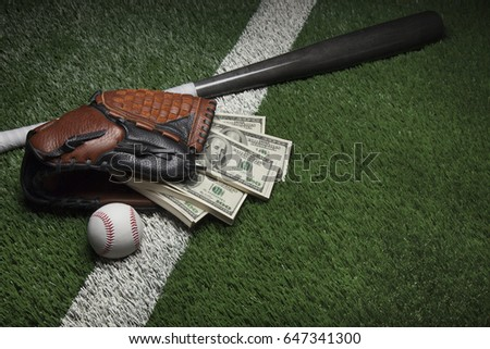 A baseball mitt full of hundred dollar bills on a field with a bat and ball