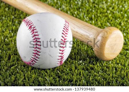 A baseball near a bat over green grass - stock photo