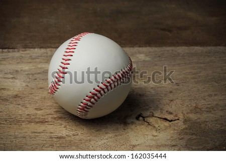 A baseball on an old wood table - stock photo