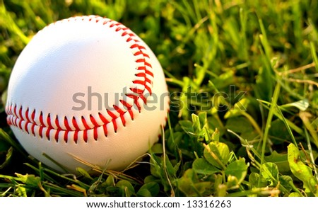 A baseball on the outfield grass backlit by the setting sun. - stock photo