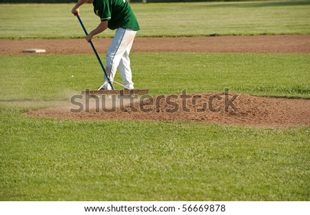 a baseball player rakes smooth the pitcher's mound