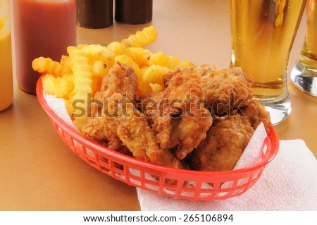 A basket of chicken wings and french fries - stock photo
