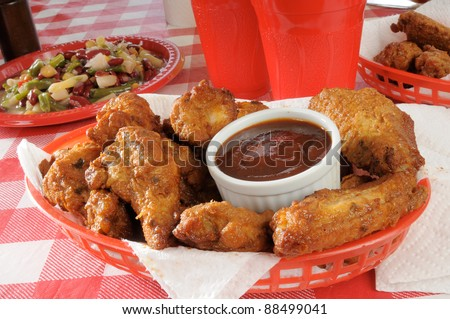 A basket of chicken wings on a plastic picnic tablecloth