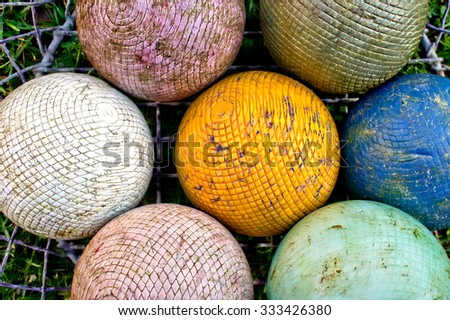 A basket of colorful croquet balls on a lawn - stock photo