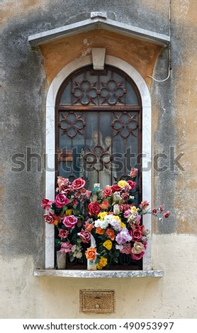 A basket of colorful flowers on the window of an ancient building in Venice, with old statuette of St. Mary and baby Jesus behind the glass