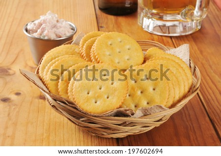 a basket of crackers with deviled ham and a mug of beer - stock photo