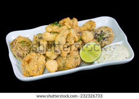 A basket of crispy chicken fingers with platter of vegetables and ranch dip on a white plate