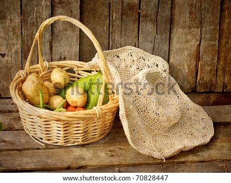 A basket of fresh picked organic vegetables and a straw hat on a grunge wood background, textured. - stock photo