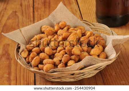 A basket of honey roasted peanuts on a wooden bar counter with a bottle of beer - stock photo
