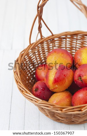 a basket of nectarines on white wooden table