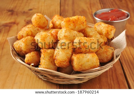 A basket of tater tots on a rustic wooden counter - stock photo