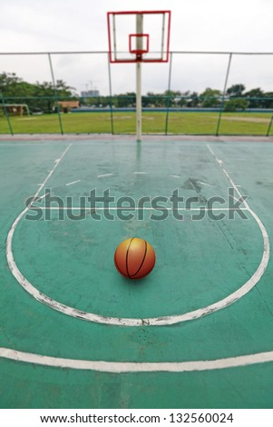 A basketball on the game court penalty free throw line facing the basket hoop in an outdoor urban park. - stock photo