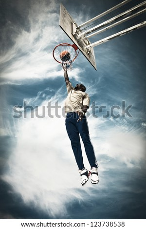 A basketball player drives to the hoop for a slam