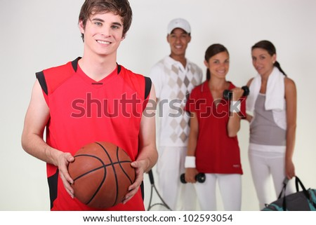 A basketball player posing with other athletes - stock photo