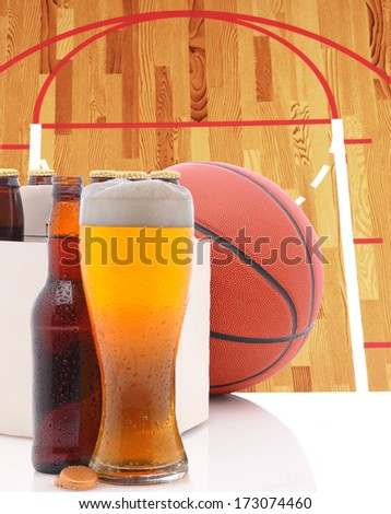 A Basketball Six Pack of Beer Bottles and a Glass of Ale on a white table top with Court in background. Great for NBA or March Madness themed projects. - stock photo