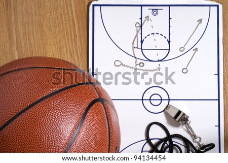 A basketball with a whistle and clipboard with an alley-oop play drawn - stock photo