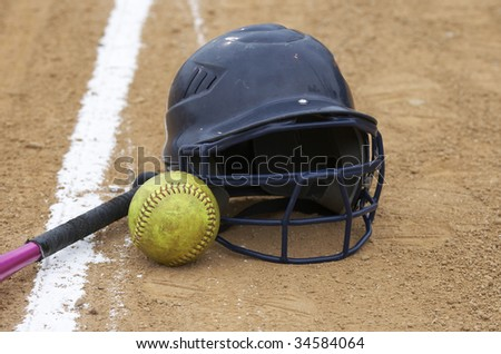 a bat, softball, and helmet on a sports infield - stock photo