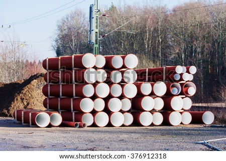 A batch of newly manufactured pipes or tubes with red on the outside and white on the inside. Electric wires for the railroad and a pile of gravel in background on industrial area. - stock photo