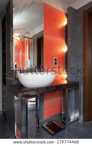 A bathroom sink by a wall with orange tiles - stock photo