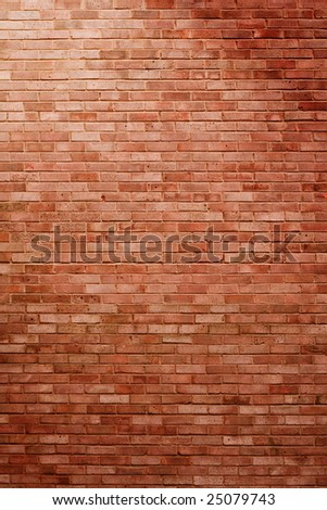 A battered brick wall in diagonal spotlight in portrait orientation, light coming from top left