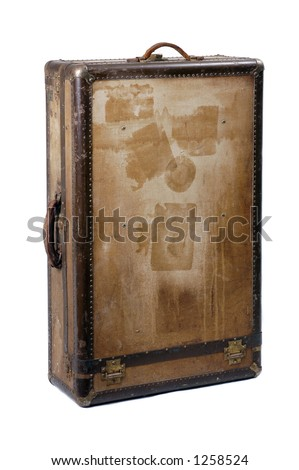 A battered old suitcase shows the traces of luggage labels from world travel, standing upright
