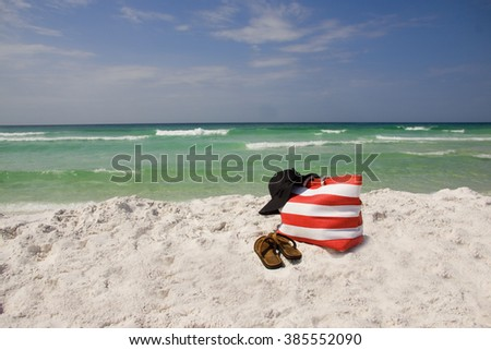 A beach bag , hat and sandals lying on the beach.
