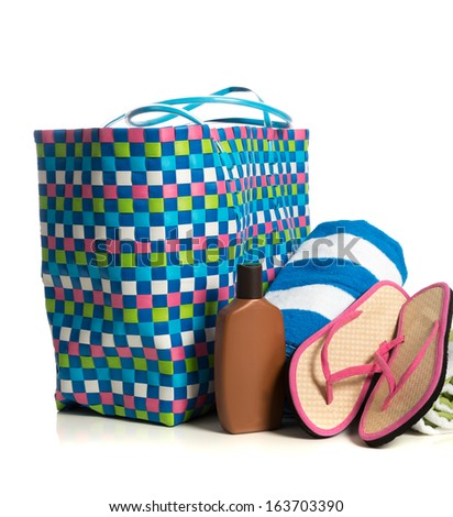 A beach bag with a striped towel, suntan lotion and pink flip-flops on a white background - stock photo