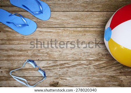 a beach ball, goggles and sandals on a dock  - stock photo