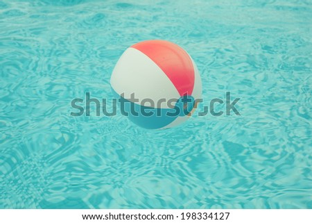 A beach ball is floating in a swimming pool
