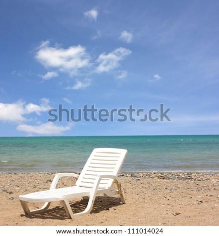 A Beach chair with a sunny blue sky - stock photo