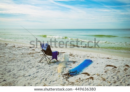 A Beach Chair with Fishing Rod and Fishing Nets on the Beach of Anna Maria Island, Florida - stock photo