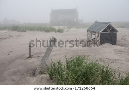 A beach house, built on the outer beach of Chatham, Massachusetts, is in danger of being washed away by the Atlantic Ocean. The beach is eroding and sea level is rising as climate change proceeds. - stock photo
