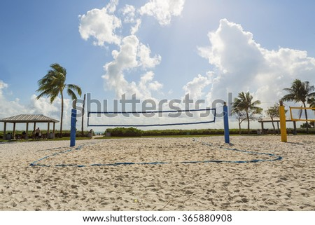 A beach volleyball net on a sunny beach, with palm trees. Florida  - stock photo