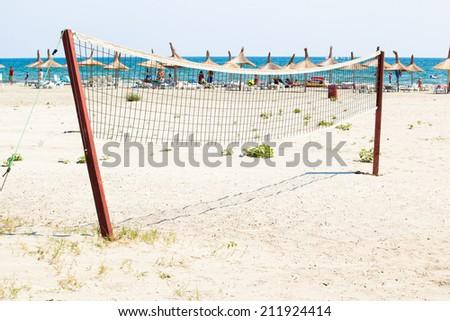 A beach volleyball net on the beach - stock photo