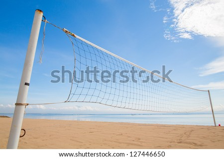 A beach volleyball net on the beach with a clear and sunny sky - stock photo