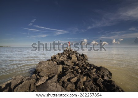 A Beacon at the Tip of the Rocky Path - stock photo